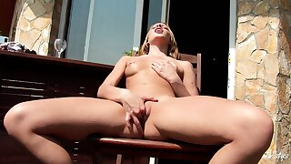 Blonde likes the outside and sits on her balcony fingering her doodle-sack